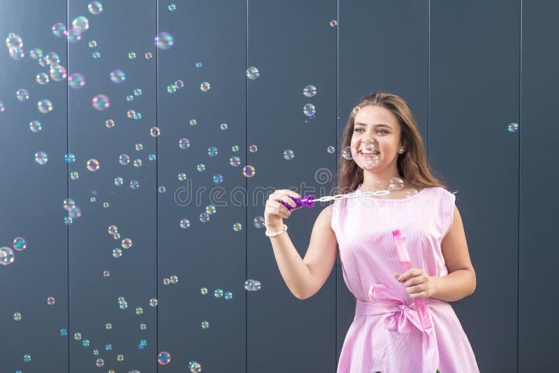 Пузыри мыла девочка-подростка дуя против серой стены стоковые изображения rf