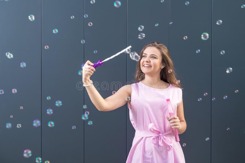 Пузыри мыла девочка-подростка дуя против серой стены стоковое изображение rf
