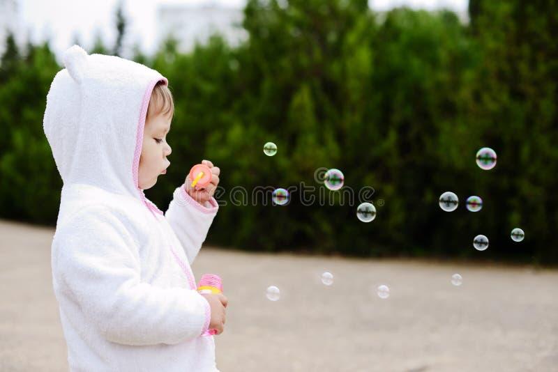 Пузыри мыла девушки дуя стоковые фотографии rf
