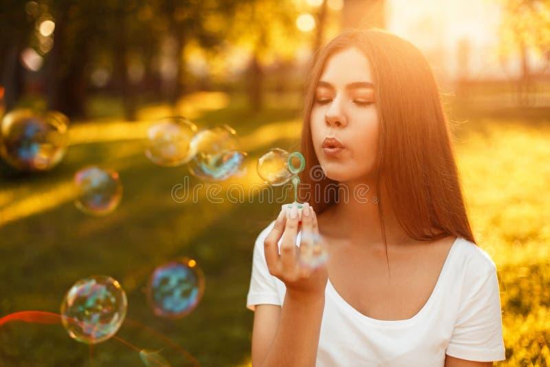 Пузыри мыла красивой маленькой девочки дуя в парке на заходе солнца стоковое изображение