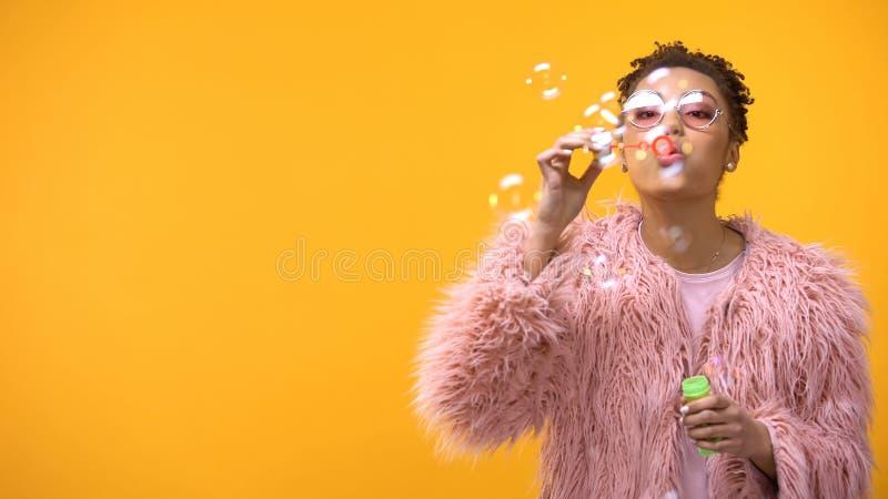 Пузыри мыла шаловливого женского подростка дуя на желтой предпосылке, партии молодости стоковые изображения