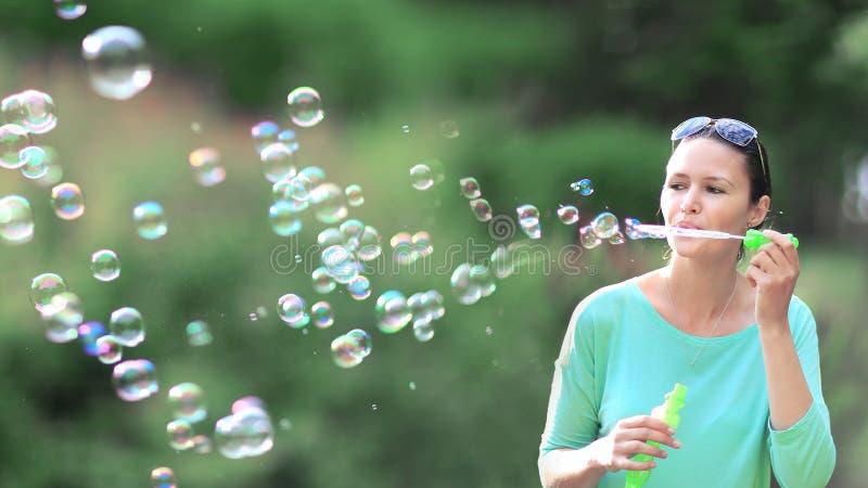 Пузыри мыла шикарной молодой девушки брюнет дуя в sunlit парке стоковое изображение