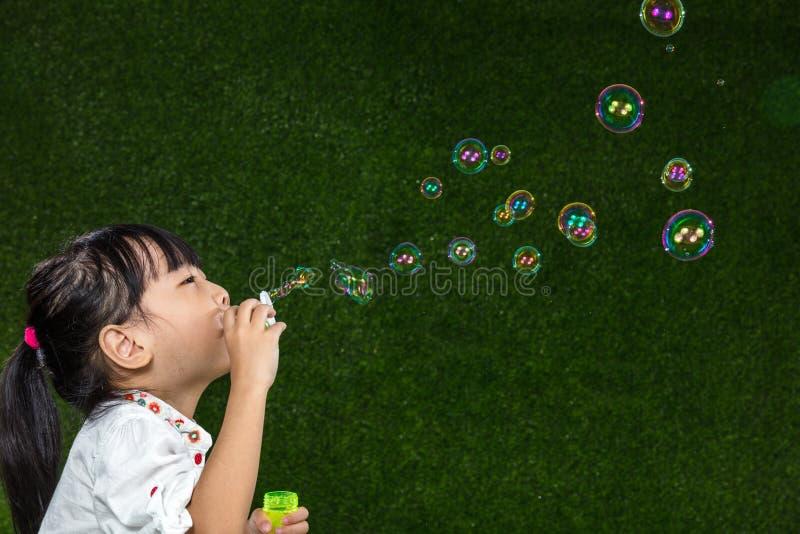 Пузыри мыла азиатской китайской маленькой девочки дуя стоковые фотографии rf