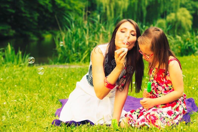 Пузыри мыла матери и ребенка дуя внешние стоковые фото