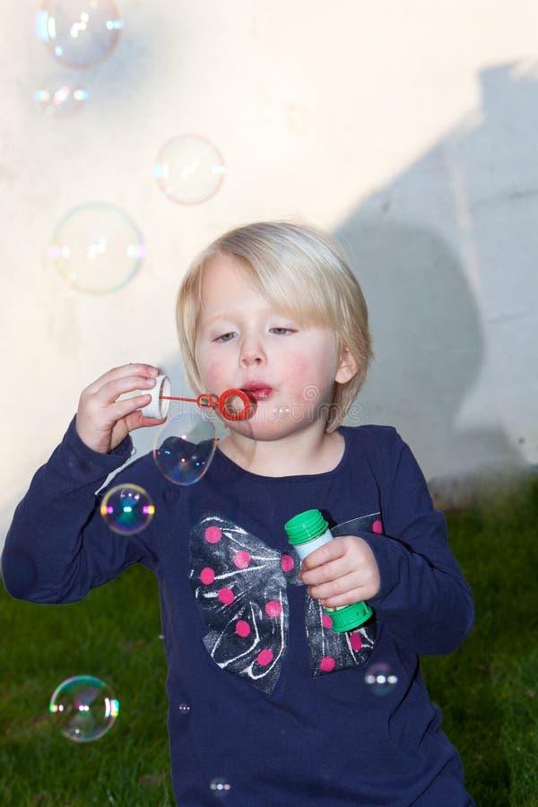 Пузыри мыла довольно маленькой белокурой девушки дуя стоковое изображение rf