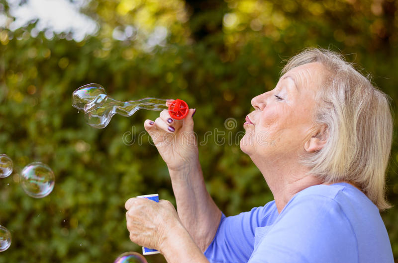 Пузыри мыла привлекательной старшей женщины дуя стоковое фото rf