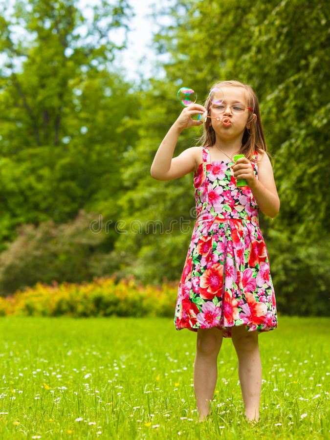Пузыри мыла ребенка маленькой девочки дуя внешние стоковые изображения rf