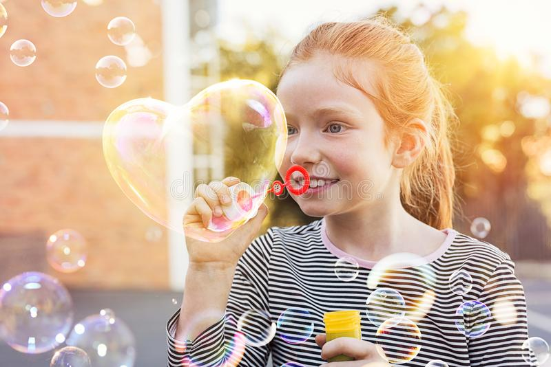 Пузырь сердца дуновения маленькой девочки стоковое фото