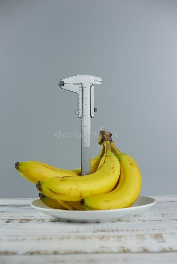 Пук бананов и крумциркуля на деревянной предпосылке r стоковые изображения