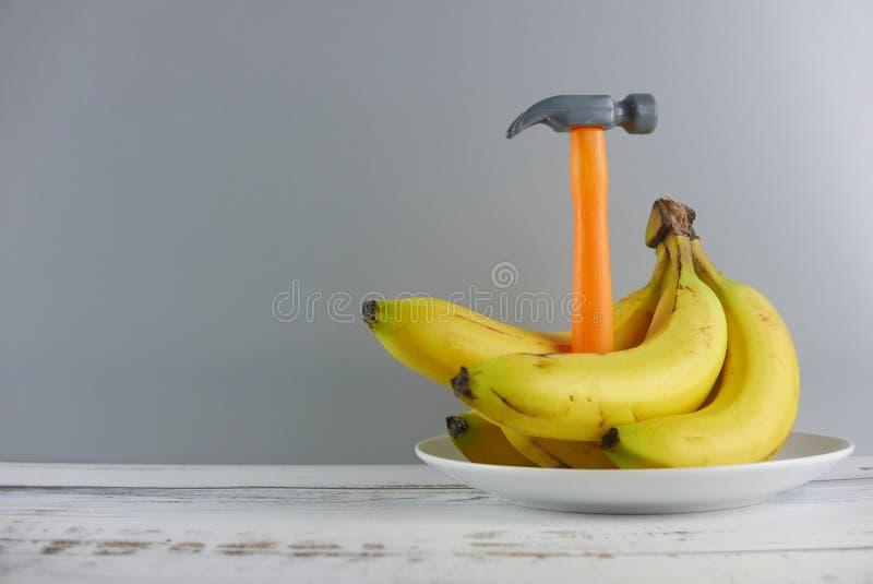 Пук бананов и молотка на деревянной предпосылке Космос экземпляра для текста или логотипа стоковые фотографии rf