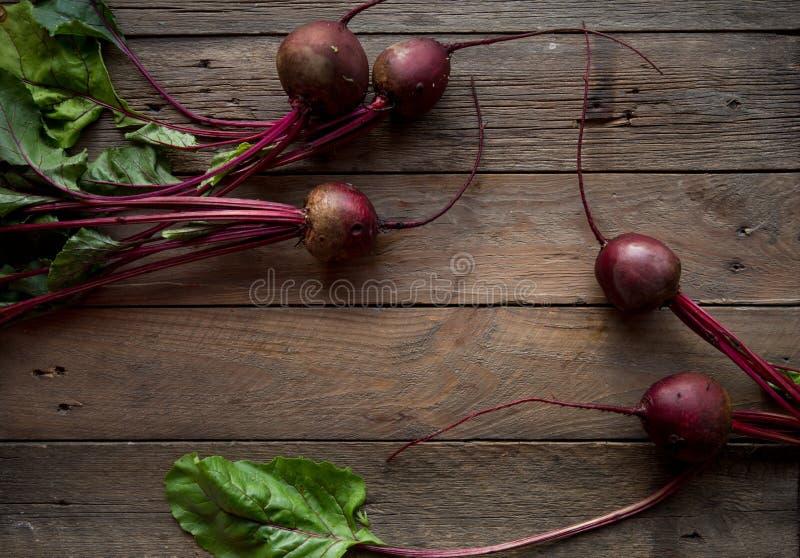 Пук бураков Свежие моркови, куча бураков с зелеными стержнями Сырцовые моркови и бураки на деревенской деревянной задней части стоковая фотография rf