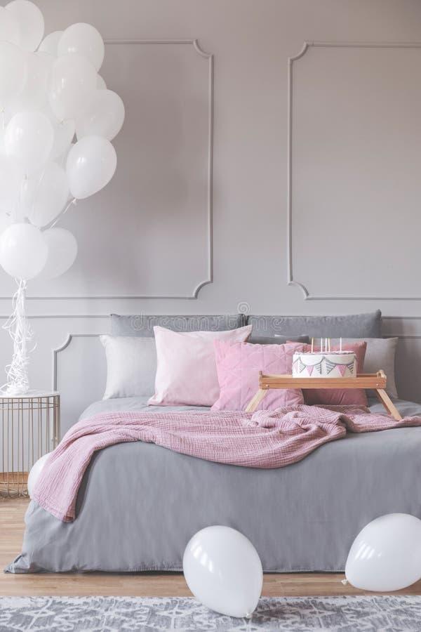 Пук воздушных шаров в элегантном сером интерьере спальни с королевской кроватью с серыми постельными принадлежностями и розовыми  стоковое фото rf