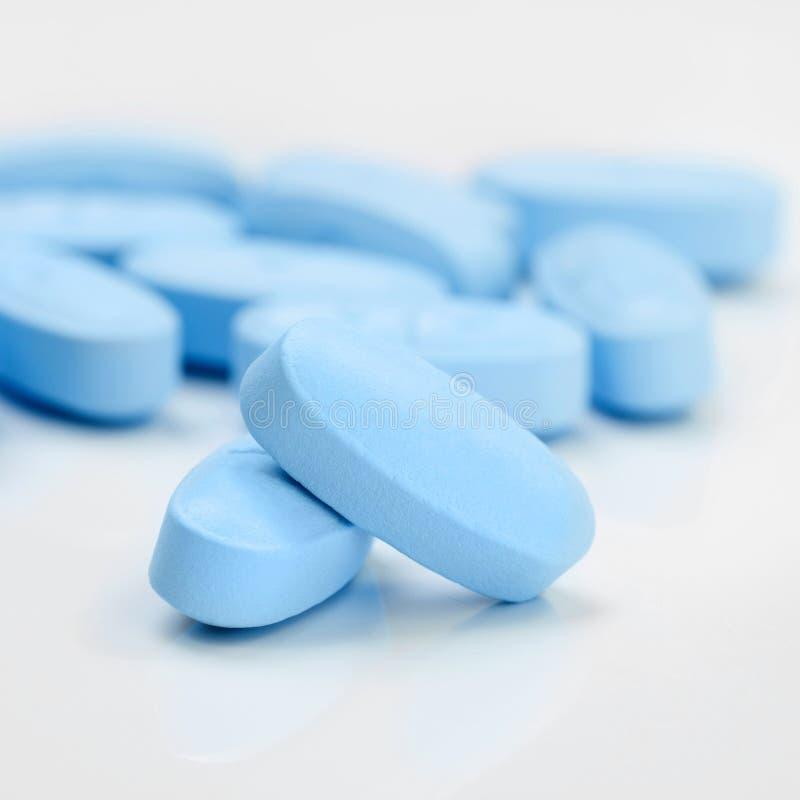 Пук голубых пилюлек на серой таблице - один против одного коэффициент стоковое изображение rf