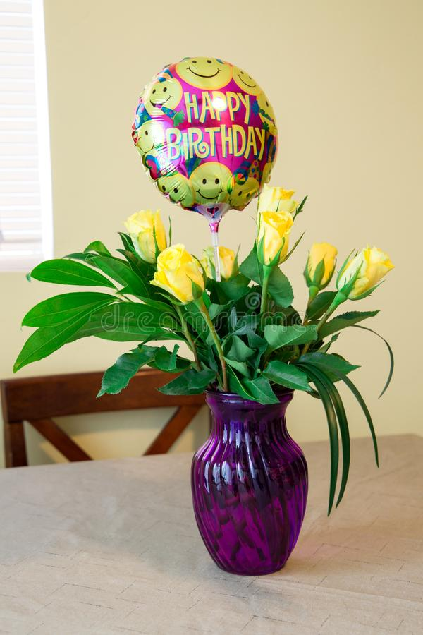Пук дня рождения желтых роз в фиолетовой вазе перед окном стоковое фото rf