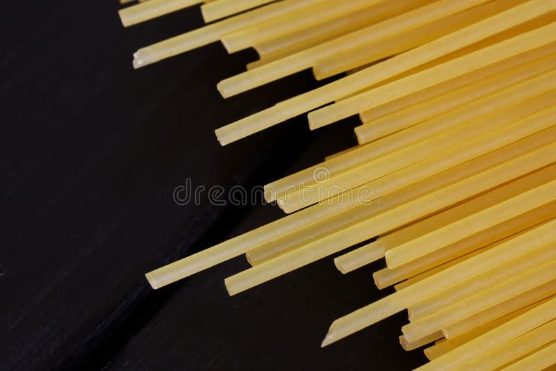 Пук золотых лож спагетти на черной деревянной предпосылке minimalism стоковое фото rf