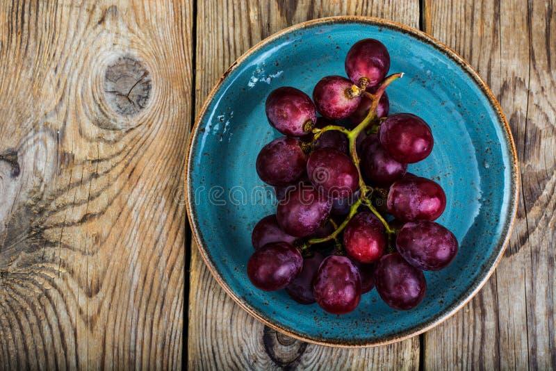 Пук красных виноградин на плите стоковые изображения