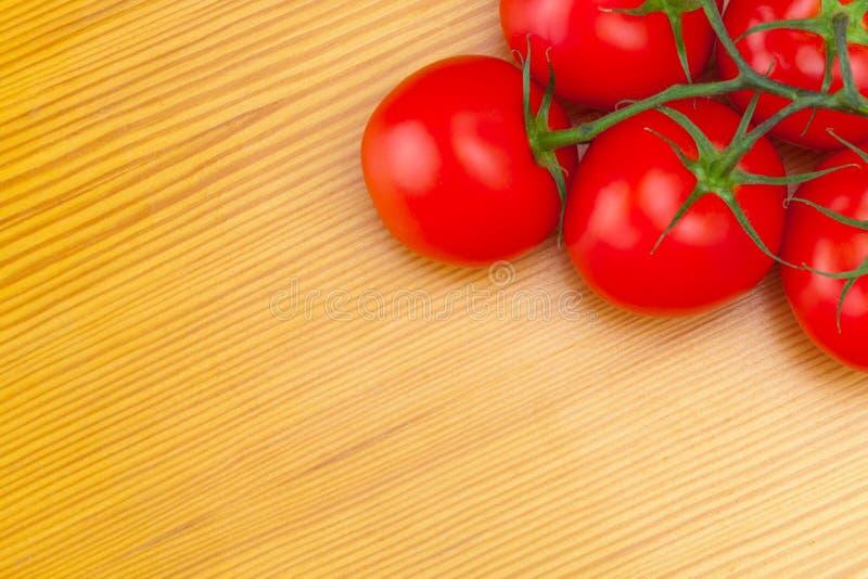 Пук красных томатов на деревянном столе - взгляд от верхней части стоковое фото rf