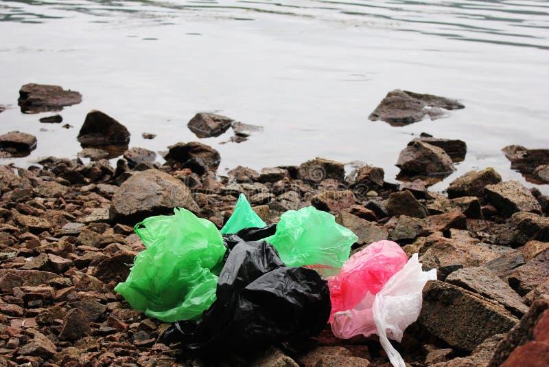 Пук многоразовых, пестротканых полиэтиленовых пакетов загрязняя окружающую среду Отброс на seashore стоковое фото