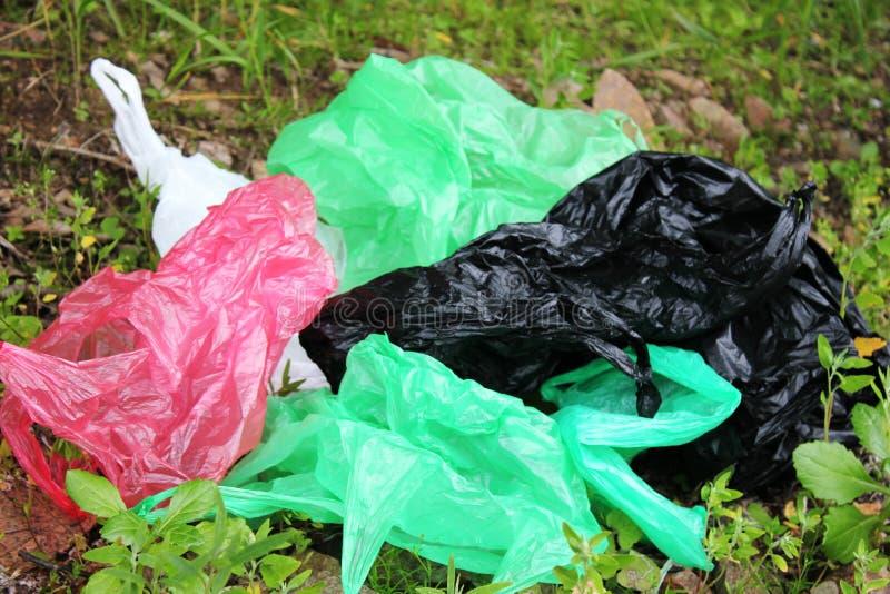 Пук многоразовых, пестротканых полиэтиленовых пакетов загрязняя окружающую среду Отброс на зеленой траве стоковое фото