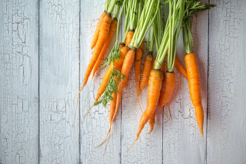 Пук морковей Свежие моркови, куча бураков с зелеными стержнями Сырцовые моркови и бураки на деревенской деревянной задней части стоковая фотография rf