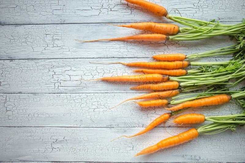 Пук морковей Свежие моркови, куча бураков с зелеными стержнями Сырцовые моркови и бураки на деревенской деревянной задней части стоковые изображения