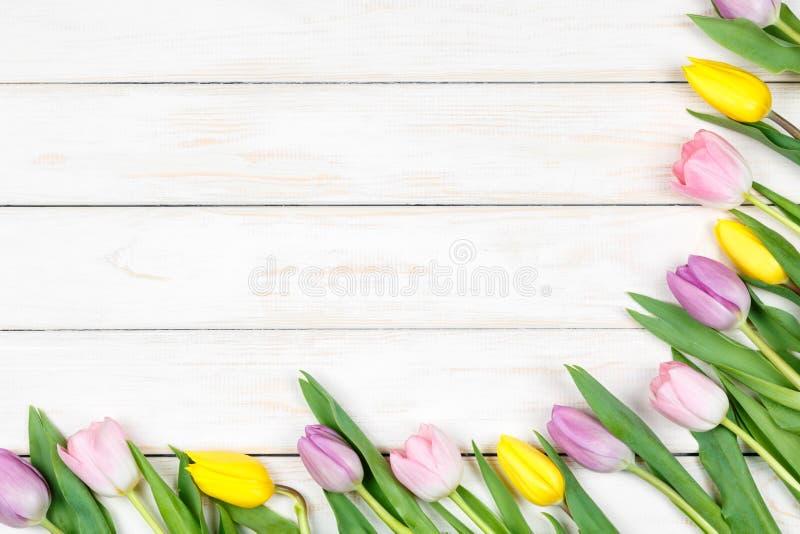 Пук розовых и желтых тюльпанов лежа на белом деревянном backgrou стоковое фото rf