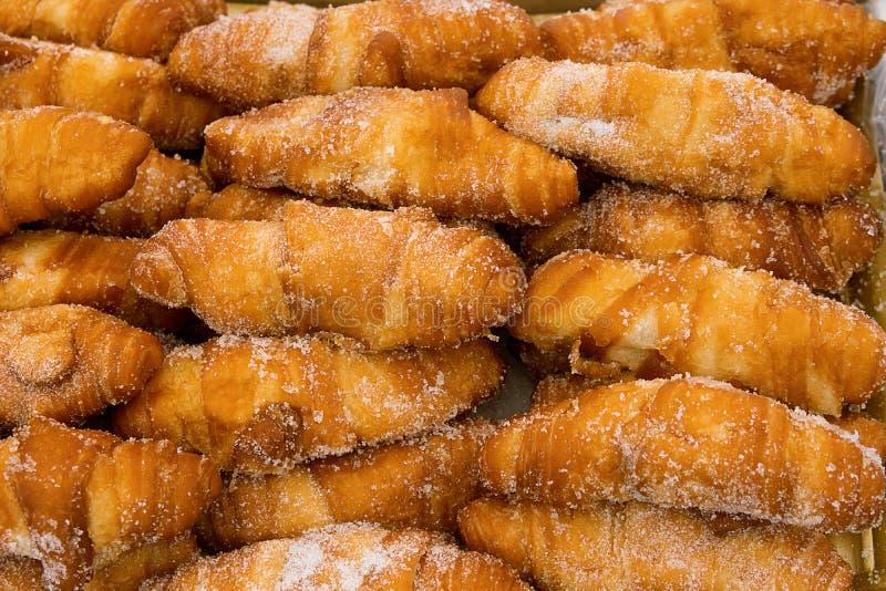 Пук свежо испеченных очень вкусных глубоких зажаренных cronuts круассанов запыленных с сахаром Печенье аппетитной золотой коркы а стоковые фото