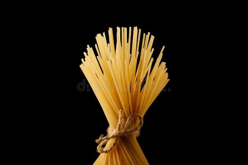 Пук спагетти связанных с веревочкой итальянский желтый цвет макаронных изделия Длиннее спагетти Изолировано на черной предпосылке стоковые фото