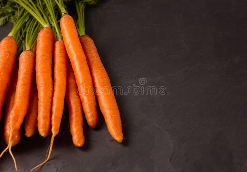 Пук сырцовых морковей на темной предпосылке стоковая фотография