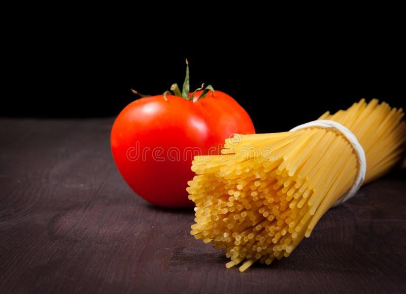 Пук сырцовых спагетти макаронных изделий с томатом на деревянной таблице стоковые изображения