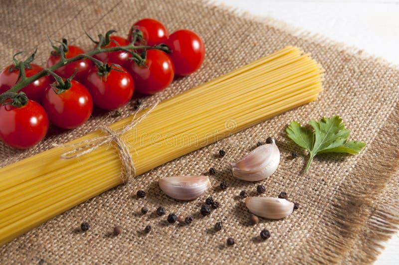 Пук сырцовых спагетти, томатов вишни, перцев, гвоздик чеснока и лист петрушки на мешковине на белой деревянной предпосылке Конец- стоковое фото rf