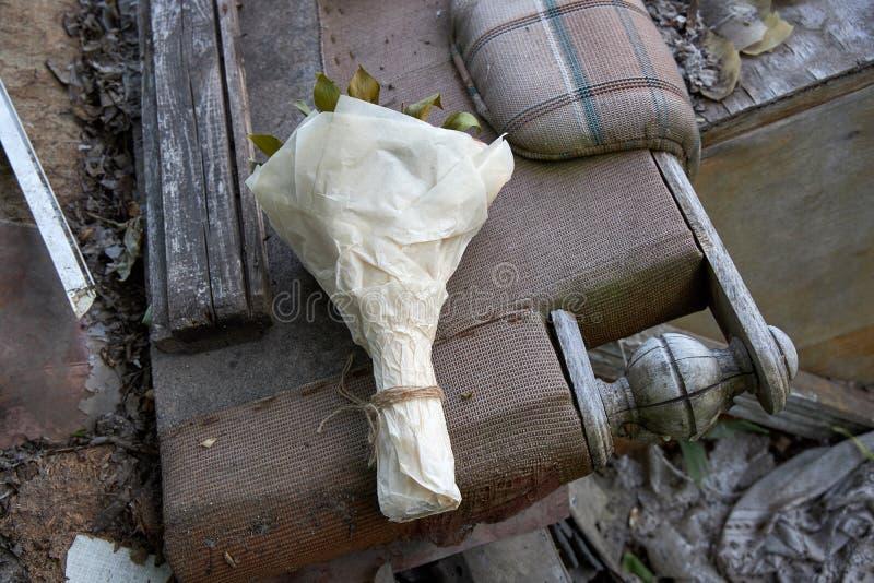 Пук цветков лежит на старой сломленной мебели как символ вздымаясь памятей стоковое изображение