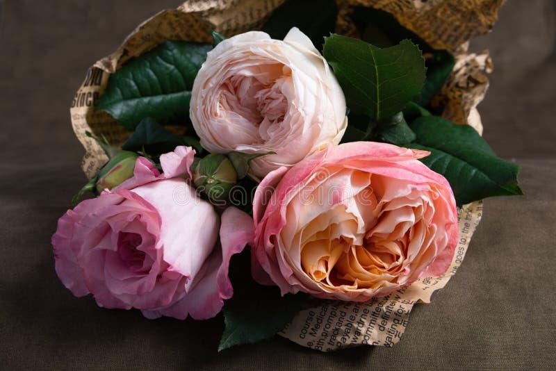 Пук чувствительных роз обернутых в газете стоковая фотография rf