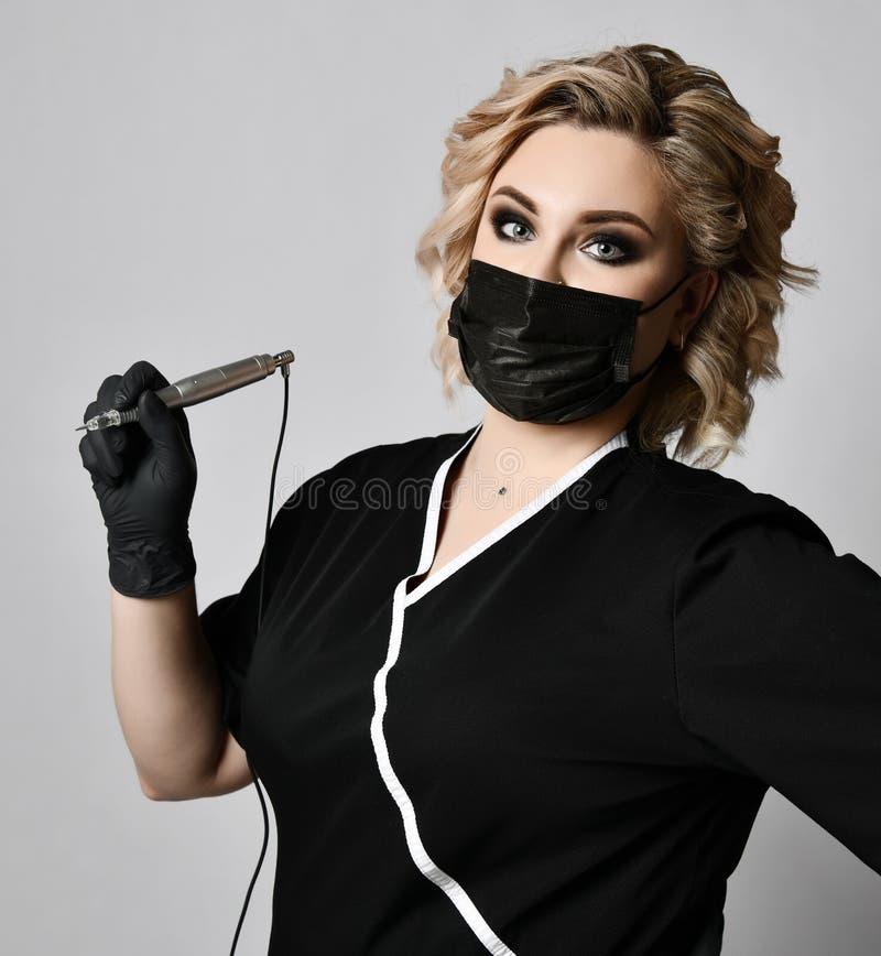 Пулемет татуировки владением cosmetologist beautician женщины в черной маске на сером цвете стоковое фото