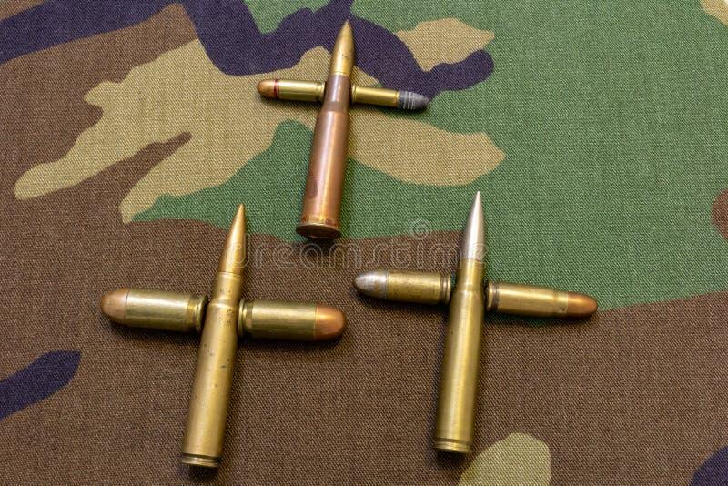 Пули винтовки и пистолета собрали совместно в форме креста Концепция войны Военная съемка предпосылки ткани стоковое изображение rf