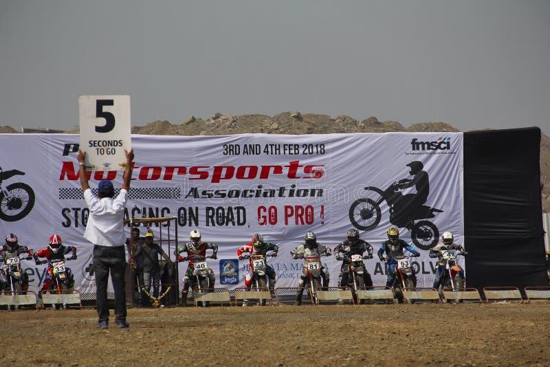 ПУНА, МАХАРАСТРА, ИНДИЯ, февраль 2018, человек показывает доску времени к участникам к гонке мотоцикла старта стоковое изображение rf