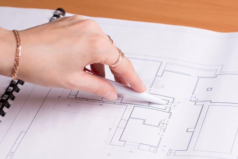 Пункты девушки к плану квартиры стоковое изображение