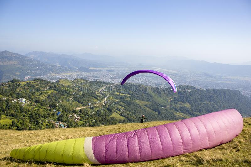 Пурпурное зеленое крыло парашюта лежит на горном склоне на фоне параплана принимая в долину горы стоковое фото rf