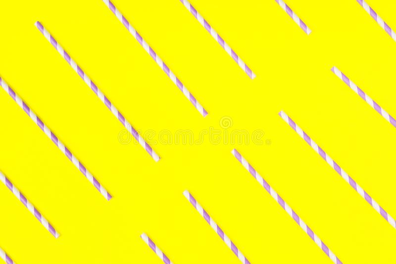 Пурпурные бумажные соломы на желтой предпосылке цвета стоковые изображения