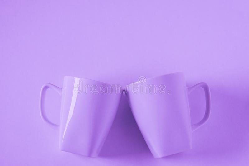 Пурпурные кружки кофе на пурпурной предпосылке clinking в приветственных восклицаниях с пустым космосом экземпляра стоковая фотография rf