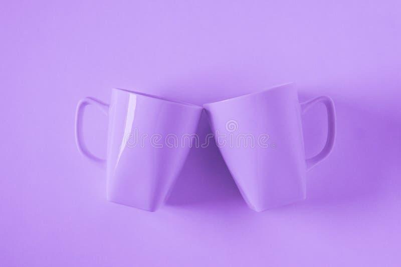Пурпурные кружки кофе на пурпурной предпосылке clinking в приветственных восклицаниях с пустым космосом экземпляра стоковые изображения rf