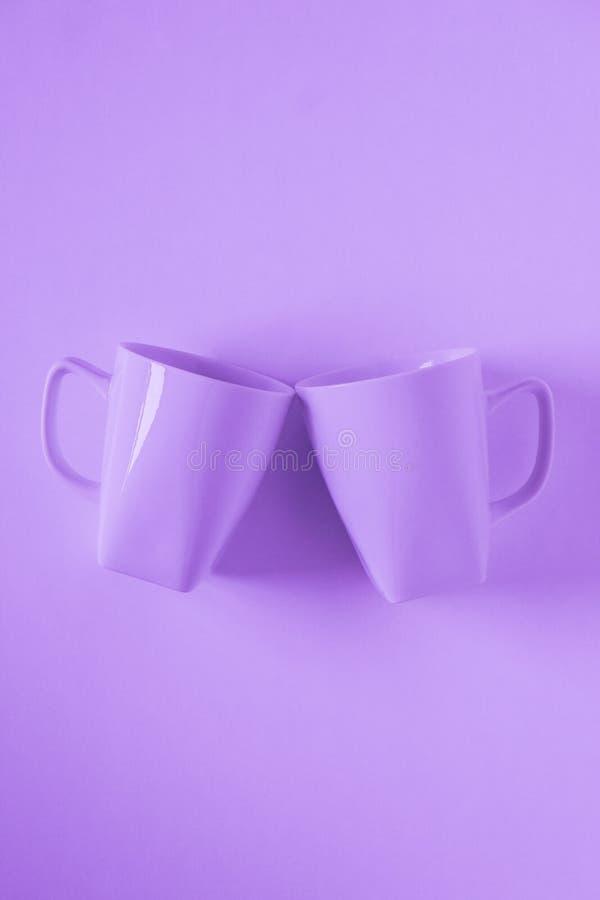 Пурпурные кружки кофе на пурпурной предпосылке clinking в приветственных восклицаниях с пустым космосом экземпляра стоковое изображение