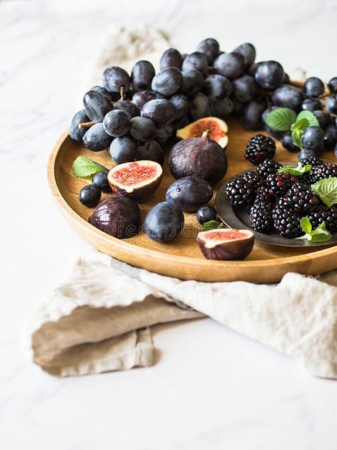 Пурпурные плоды, ягоды и зеленые листья мяты Ежевики, виноградины, сливы и смоквы в деревянном подносе на белой мраморной предпос стоковое изображение