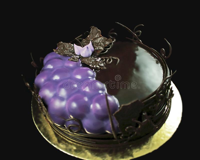 Пурпурные украшенные виноградины и шоколадный торт с границей лоз шоколада на золотом каботажном судне стоковая фотография