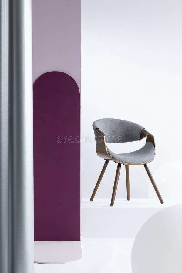 Пурпурный штендер рядом с серым стулом в яркой квартире стоковые изображения rf