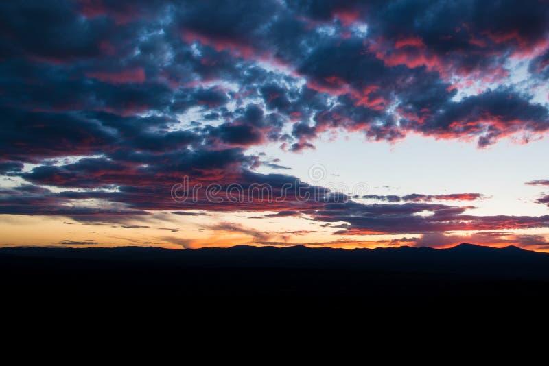 Пурпур и пинк конспектируют красивые облака на заходе солнца над горной цепью silhouetted против неба стоковая фотография
