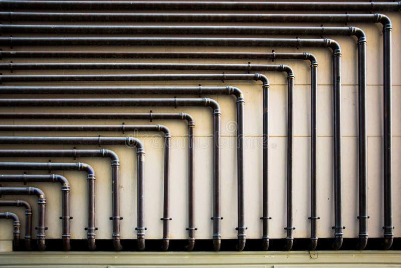 Пускать по трубам на стене с геометрическими формами стоковое фото rf