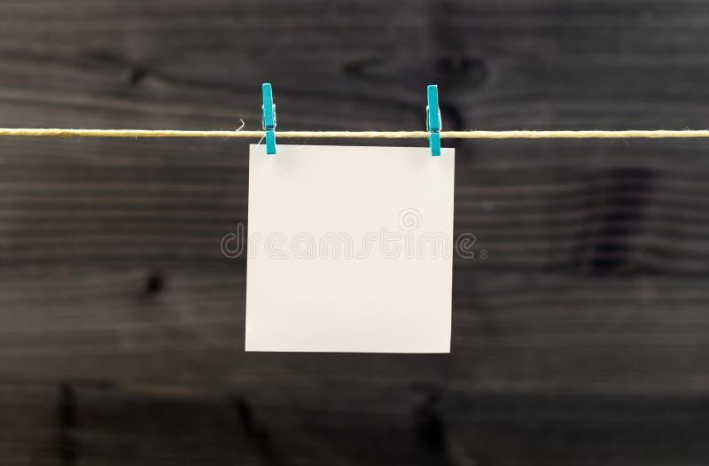Пустая белая бумага вися на веревочке с зажимками для белья против деревянного фона стоковые фотографии rf