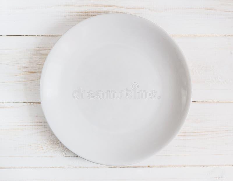 Пустая белая плита на белой деревянной предпосылке стоковые изображения rf