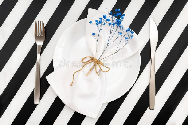 пустая белая плита с салфеткой и цветками в форме смычка и нож вилки на черной белой таблице нашивок стоковые фотографии rf